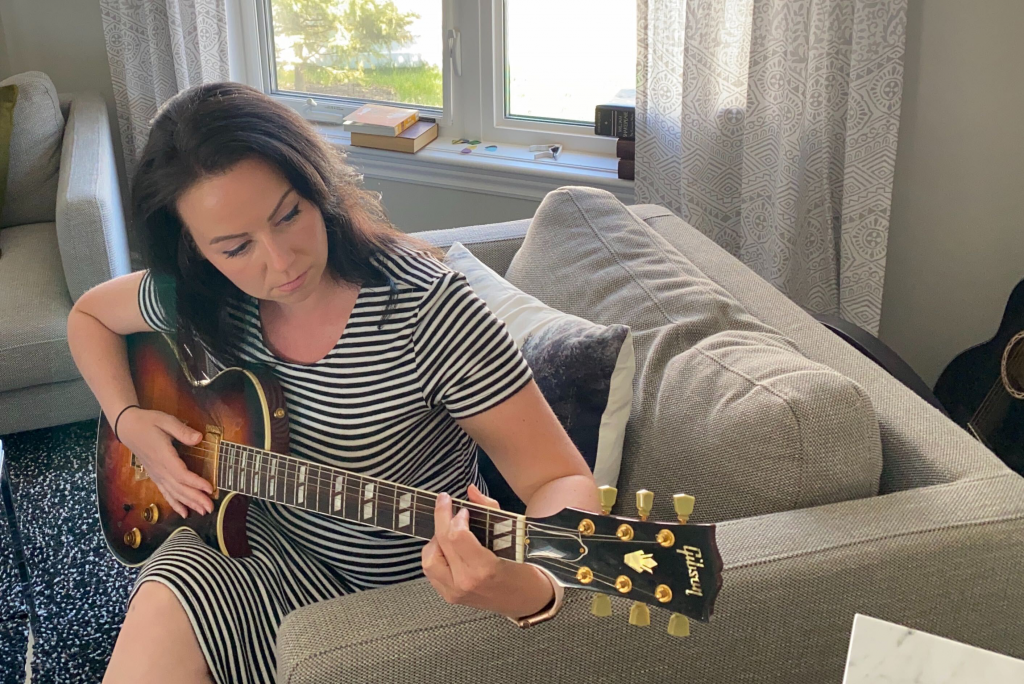 Bandzoogle CEO Stacey Bedfor plays guitar in her home.